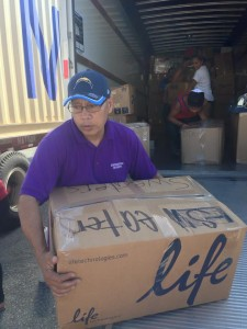 Patrick Cabrera loads boxes of donated items bound for the CNMI